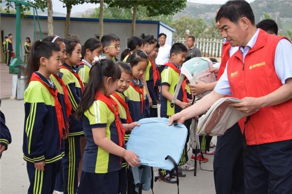 青州农商行志愿者发放爱心书包